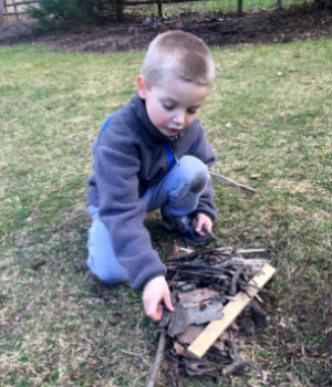 During outdoor self-directed playtime, a boy builds a pile of sticks.