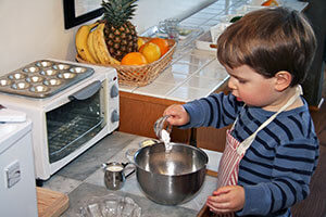 A young child cooks independently, following the principles of creating space for children.
