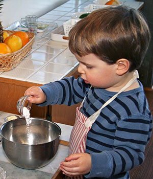 A boy mixes together ingredients while cooking, demonstrating the principle of creating space for children