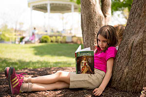 A girl reads under a tree while learning emotional balance