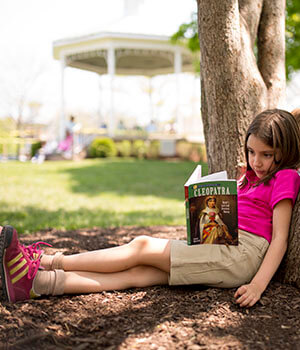 A girl reads a book under a tree while learning emotional balance
