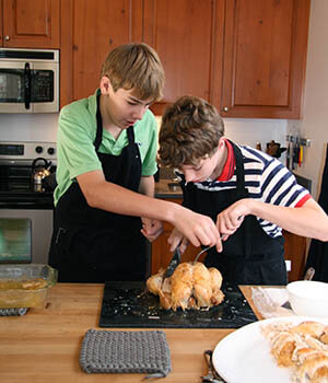 Two adolescent boys in aprons carve a turkey together, practicing for one of their holiday family traditions
