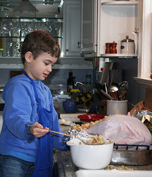 A child stands at the kitchen counter, assisting to prepare the Thanksgiving turkey, in one of his family holiday traditions of cooking together.