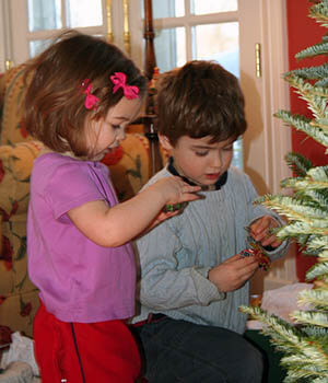 Young children decorate a Christmas tree together as part of their family holiday traditions.