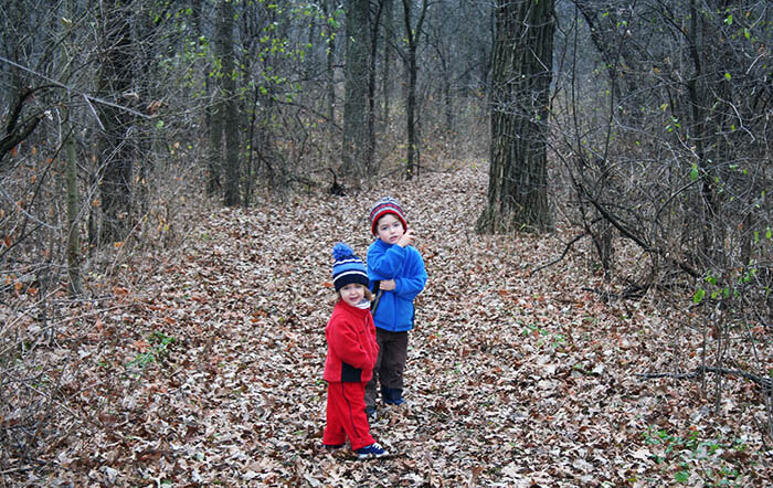 Two children bundled in winter coats walk together in the woods as part of their family holiday traditions.