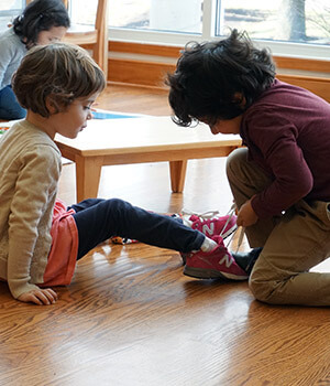 A little boy helps his classmate to tie her shoes, part of his process to develop moral values