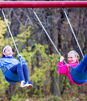 Two girls swing together on a swing set, building connections that can weather the uncertainties of life.