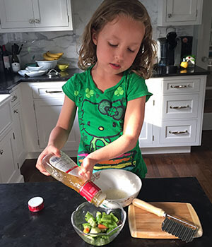 A girl helps prepare a salad, avoiding timeouts and tantrums