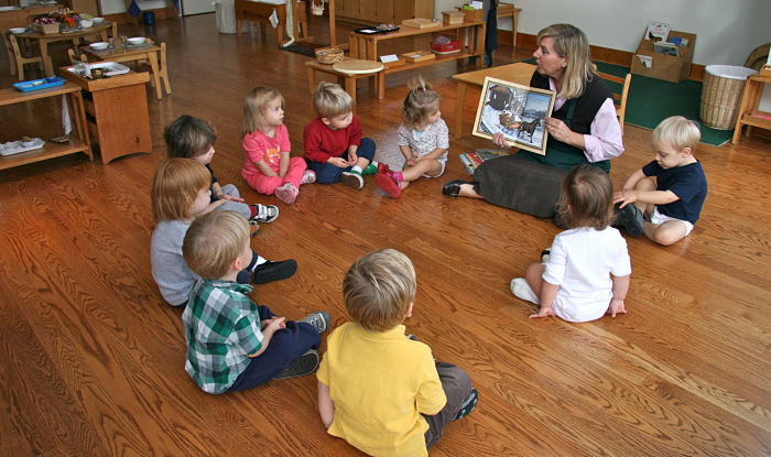 Children sitting nicely listening to Montessori teacher read, to avoid timeouts and tantrums in the classroom