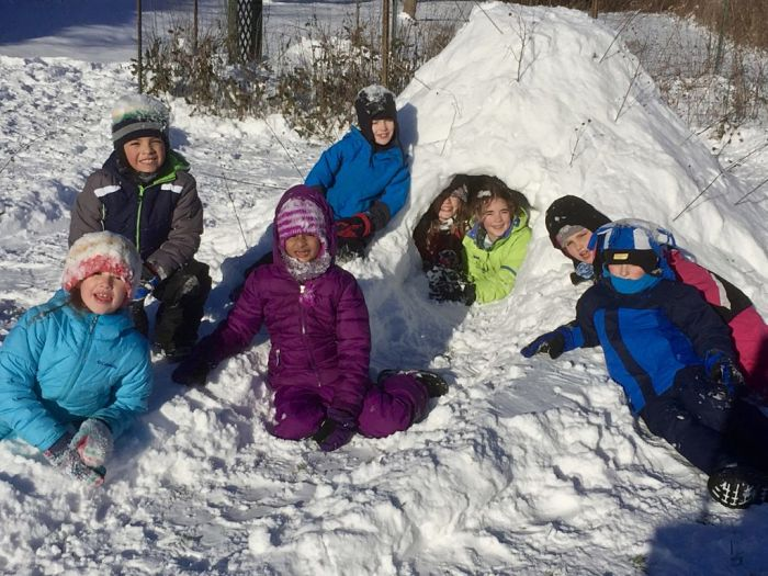Forest Bluff School children enjoy winter weather fun by building a snow fort together.