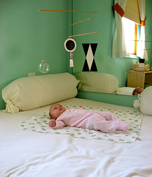 A baby focuses on her mobile, in a room inspired by Montessori classrooms