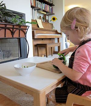 A girl focuses on work at home, in an environment modeled on Montessori classrooms