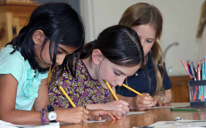 Girls concentrate on their work while in the environment of Montessori classrooms