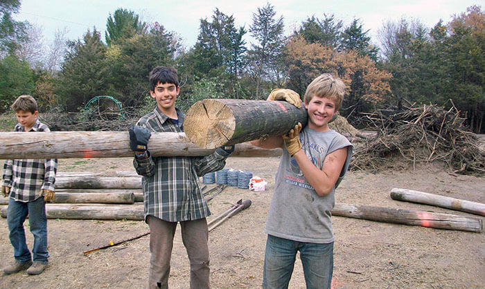 Two Secondary level boys carry heavy lumber while building happiness on a school camping and work trip.