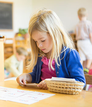 A girl works on early reading with phonogram cards in the Montessori approach to reading and writing