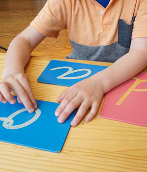 A student traces a sandpaper letter as part of the Montessori approach to reading and writing