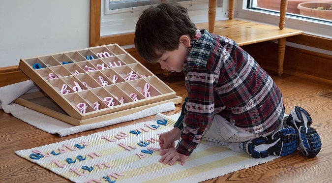 Boy working on moveable alphabet practicing the Montessori approach to writing and reading.