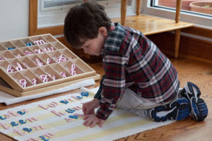 A Montessori Primary student spells words on a floor mat using the moveable alphabet.