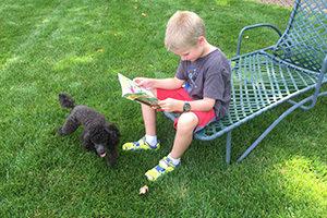 A Montessori child reads a book for pleasure outside.