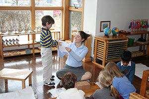 A Montessori teacher assists a students while working with a group of students.