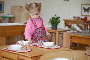 A Montessori child sets a table for a morning refreshment.