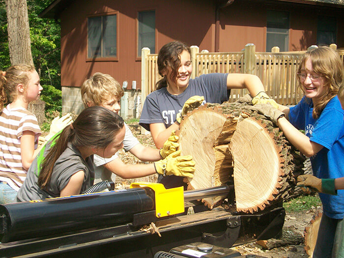 A group of adolescents are given the freedom and responsibility to use a log splitter during service work.