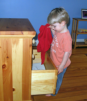 A child is given the freedom to choose his own clothing from a dresser drawer in his bedroom.
