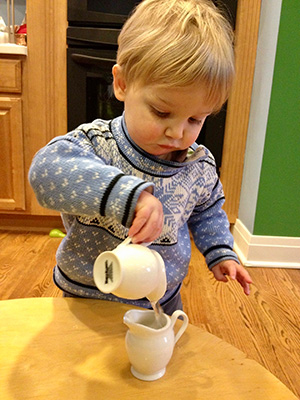 A young child pours water from one ceramic pitcher into another.