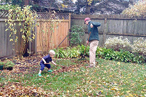 A child chooses to rake leaves with his father in the backyard of their home.