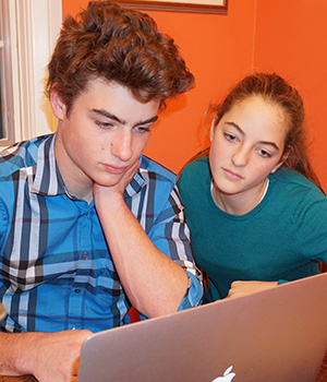 Two teens look at a laptop.
