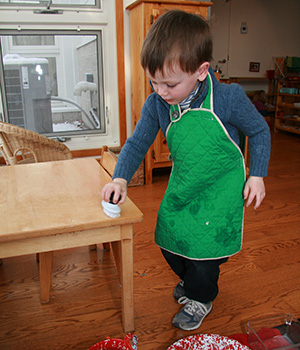 A Montessori child uses a scrub brush to wash a table.