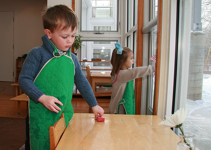 A Montessori child wipes a table clean with a sponge after scrubbing it with a scrub brush.