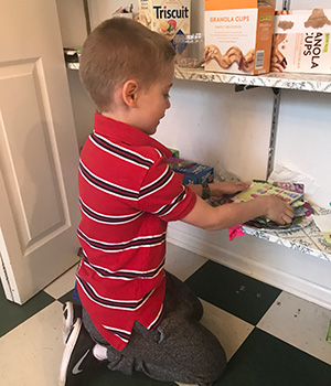A child organizes items in the pantry.