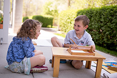 Montessori students in a Primary classroom collaborate outside at low, portable wooden tables.