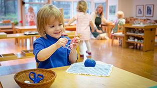 A child in a Montessori Young Children's Community sews independently.