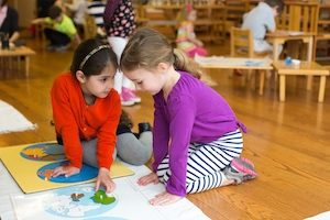 Students in a Montessori Primary classroom work together on a puzzle map of the world.
