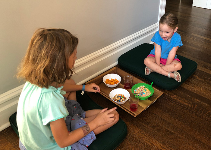 Two children use chair cushions and a serving tray on the floor to act as a table and chairs for eating a snack at home.