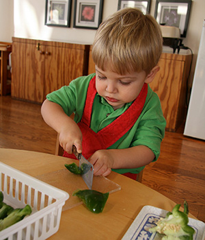 A child in a Montessori Young Children's Community independently cuts vegetables to prepare a refreshment for his class.