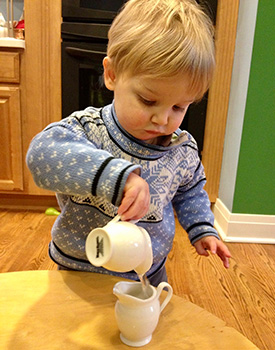 A young boy uses child-sized ceramic pitchers to pour water at a low table.