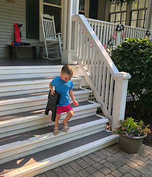 A young child carries a portable folding step stool.