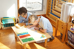 Students in a Montessori classroom work together with math materials