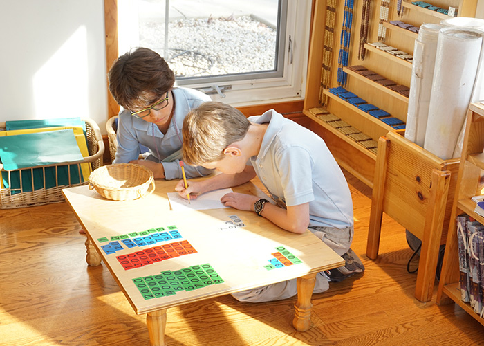 Students in a Montessori elementary classroom work together with math materials.