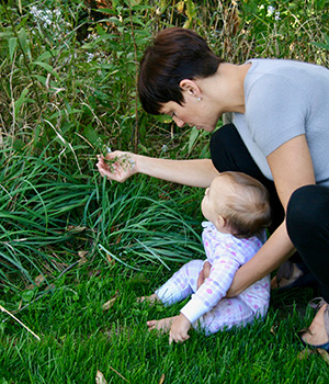 A mother shows her curious infant a flower outside.