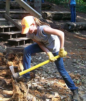 An adolescent Montessori students chops wood on a work trip