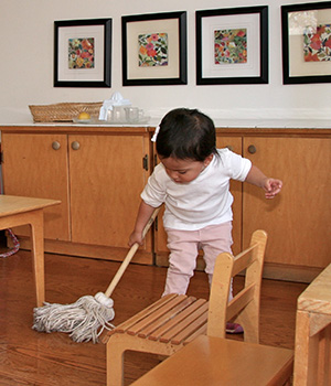 A young child in a Montessori classroom mops the floor independently.