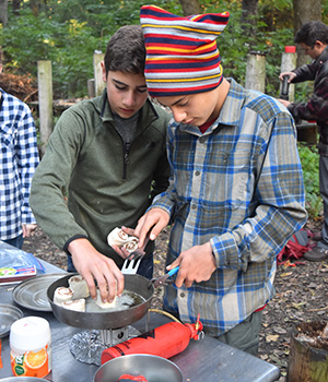 Adolescent Montessori students cook a meal on an outdoor work trip