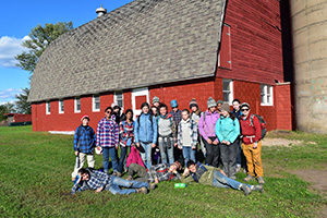 Adolescent Montessori students in front of a barn they painted on their fall work trip