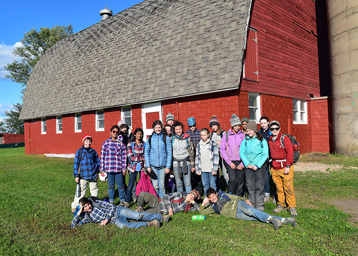 Adolescent Montessori students in front of a barn they painted on a work trip