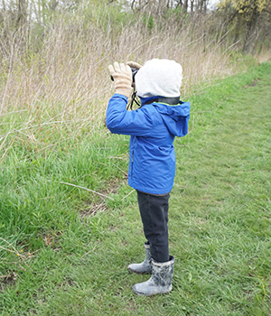 A child explores the natural environment using binoculars