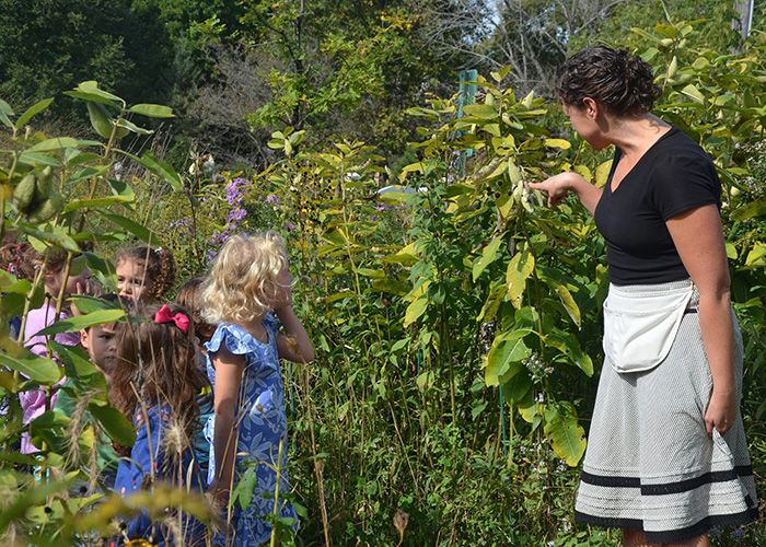 A Montessori teacher identifies native plants in the prairie with Primary Level children